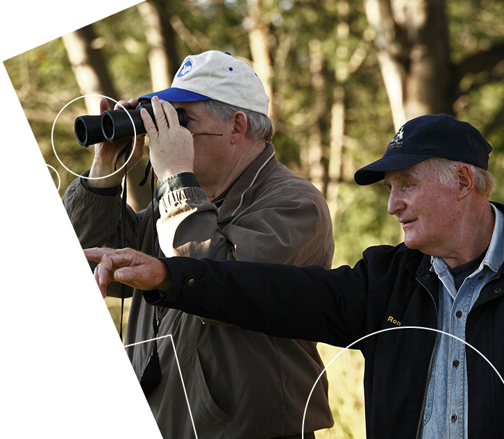 Man with binoculars with another man pointing