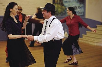 A man and woman dancing in a hall with others dancing in the background
