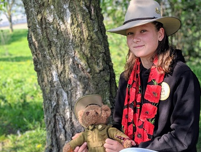 Nell Hentschel holding a teddy bear in military uniform with tree trunk as background