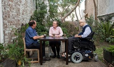 Three people seated in a garden having a discussion. The man on the right is seated in a wheelchair