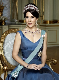 HRH Crown Princess Mary of Denmark is seated and wearing a Royal blue satin dress