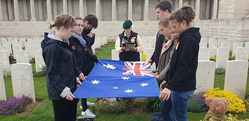 Students from the holding the Australian flag in a Commonwealth War Graves Commission cemetery as Elizabeth Perkins reads information