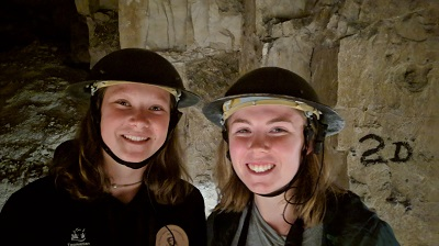 Two young women wearing helmets in a tunnel