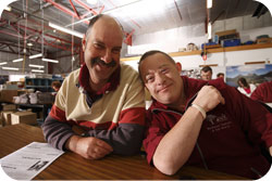 Two men seated at a work bench