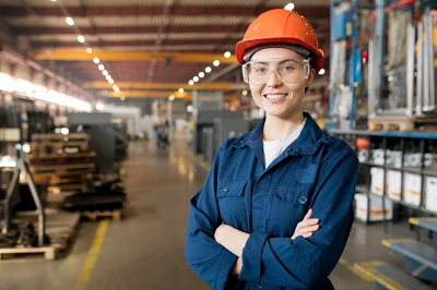 A young woman in a warehouse. She is wearing an orange helmet