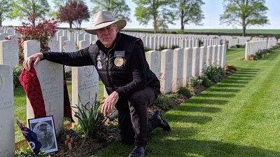 Mr Kerry Finch kneeling at the grave of Corporal Michael Manion