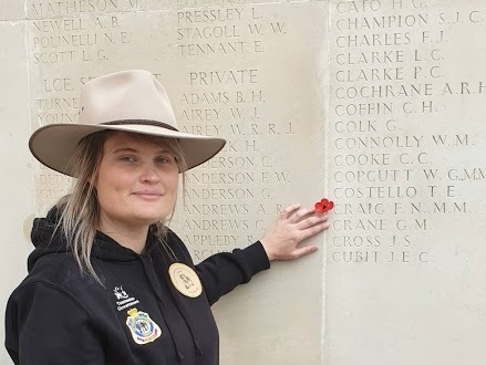 Mel Burnett points at Private Craig's name engraved on the memorial wall at Villers-Bretonneux