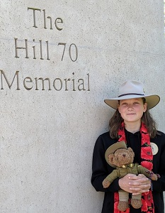 Nell Hentschel holding at teddy bear in military uniform at the Hill 70 Memorial