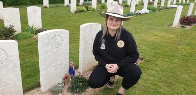 Mel Burnett kneeling at unknown soldier's grave where she has placed a flag and jar of sand